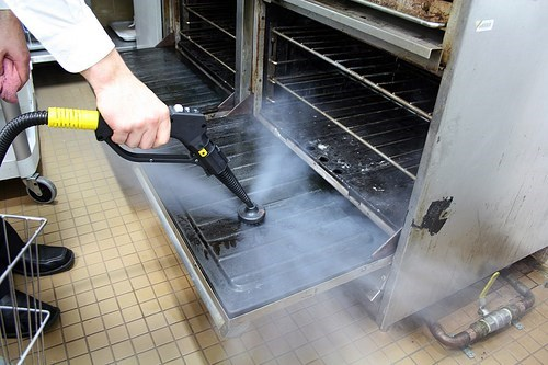 commercial oven being cleaned